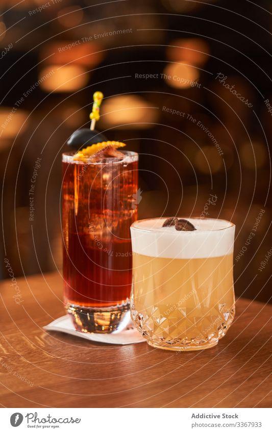 Roter Alkoholcocktail mit schwarzer Olive und Whiskey-Zitronen-Cocktail trinken klassisch rot Glas hochball Eis oliv Abfertigungsschalter Bar kalt Aperitif