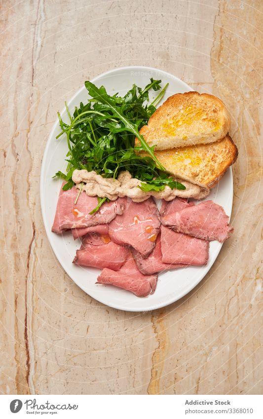 Leckeres Fleisch mit Brot und Rucola Speise Teller Schinken Jamón Restaurant frisch grün Kraut Tisch hölzern Salatbeilage Scheibe stylisch elegant Haute Cuisine