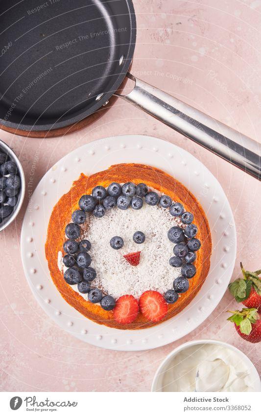 Kuchen mit Beeren auf Teller gebacken Dessert Essen zubereiten dekorierend Blaubeeren Erdbeeren Sauerrahm Frau Küchenchef selbstgemacht Haushalt Pinguin Speise
