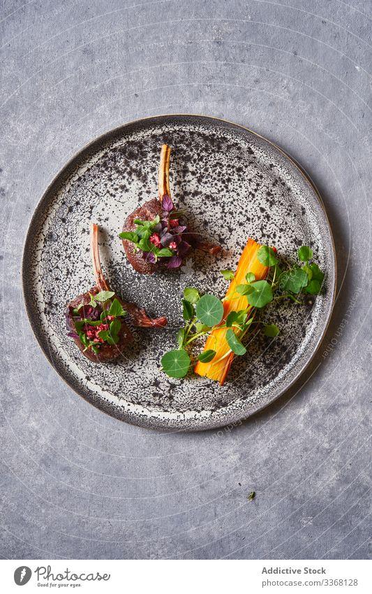 Draufsicht auf schmackhafte Fleischmedaillons mit Kräutern auf dem Teller Medaillon Saucen Kraut Lebensmittel Mahlzeit Küche geschmackvoll lecker Speise