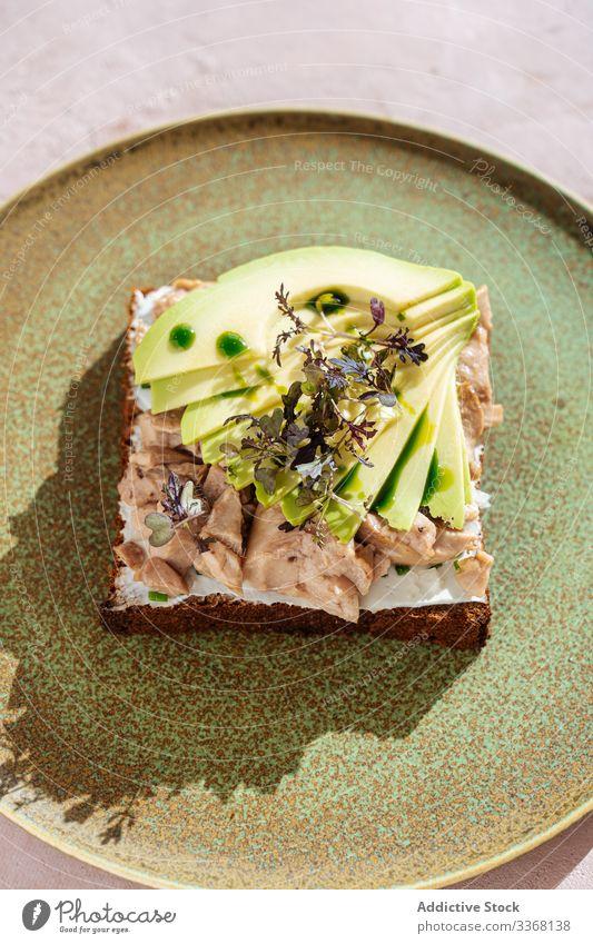 Thunfisch-Sandwich mit Avocado-Stücken Belegtes Brot Teller Kantine Tisch Frühstück Gesundheit Lebensmittel Scheibe Mahlzeit Mittagessen Küche Portion frisch