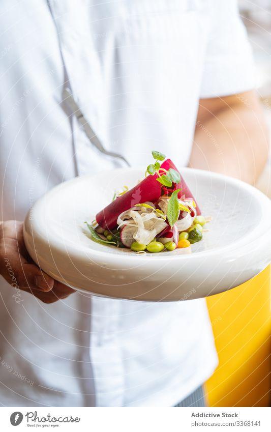 Anonyme Person, die einen exquisiten Gemüsesalat auf dem Teller hält Salatbeilage Restaurant Exquisit Lebensmittel Speise Feinschmecker Gesundheit Abendessen