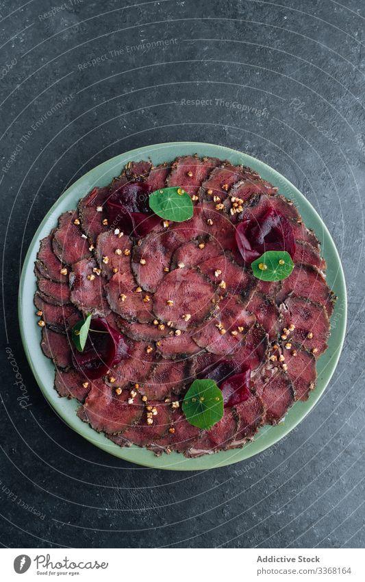 Teller mit leckerem Carpaccio im Cafe Fleisch roh Scheibe Restaurant Rote Beete Exquisit kalt Feinschmecker Amuse-Gueule Speise Lebensmittel geschmackvoll