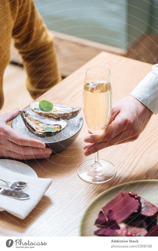 Erntehelfer genießt Austern und Champagner Person essen trinken Restaurant Zitrone Kraut Eis Tisch Muschel Meeresfrüchte Exquisit lecker geschmackvoll