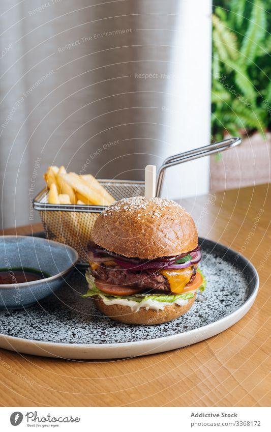 Köstlicher Burger mit gebratener Frikadelle und frischem Gemüse Fastfood Straßenessen Speise Restaurant Pastetchen Saucen Zwiebel Salat Hirschfleisch Käse