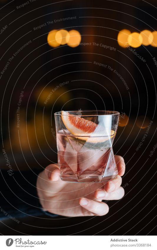 Anonyme Person mit alkoholischem Getränk mit geschnittener Grapefruit und Eis Cocktail Zitrusfrüchte Alkohol Bar Tisch trinken Tasse Glas Erfrischung kalt