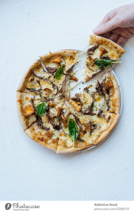Erntehelfer nimmt Stück Meeresfrüchte-Pizza Person Scheibe Käse Basilikum Pilz Speise geschmackvoll Portion versuchen Sie warm heiß Spielfigur Kraut Bestandteil