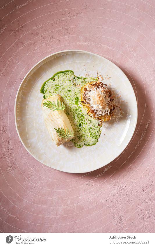 Exquisites Fischgericht auf rosa Hintergrund Saucen eingießen Speise Restaurant Löffel Kraut Abendessen Sahne Küche Lebensmittel Meeresfrüchte lecker