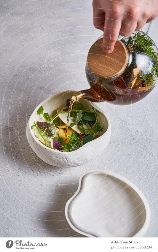 Erntehelfer gießt Tee in Schale mit Kräutern Kraut eingießen Person Teekanne Schalen & Schüsseln heiß Gesundheit trinken gebraut Getränk Tasse traditionell