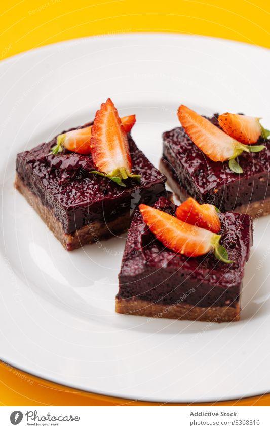 Stücke von Beeren- und Schokoladenkuchen Dessert süß Kuchen Teller Erdbeeren Spielfigur Lebensmittel Gebäck geschmackvoll Küche Speise lecker Zucker Kalorie