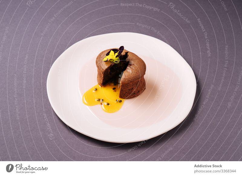 Schokoladenmuffin mit Fruchtfüllung Dessert Muffin Brotbelag Blume Teller Café süß Passionsfrucht Lebensmittel Gebäck geschnitten liquide Saucen geschmackvoll
