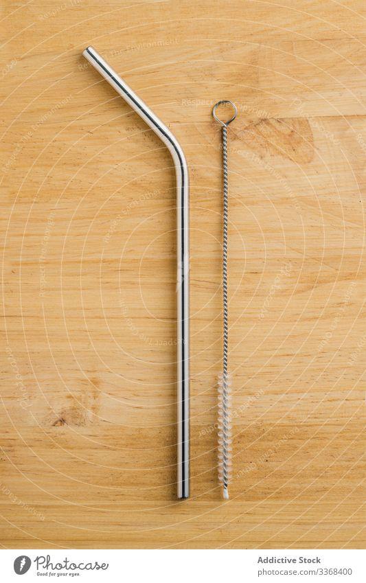 Ökologische Metall-Strohhalme und Reinigungsbürste auf dem Tisch ökologisch metallisch umweltfreundlich Bürste wiederverwendbar Reihe hölzern Stahl glänzend