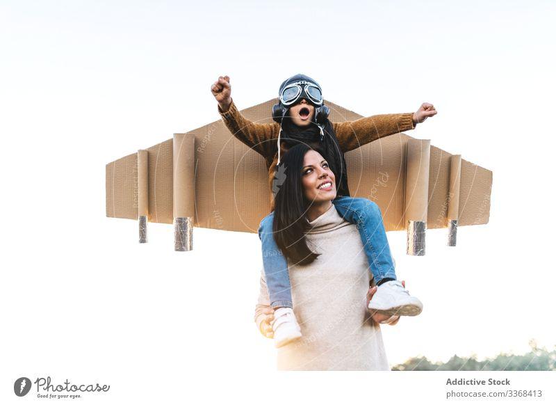 Fröhliche Mutter und Sohn spielen zusammen auf dem Feld Frau Mama Flieger träumen Spiel Zusammensein Junge anhaben Schutzbrille Flügel imitieren Wiese Karton