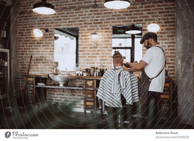 Friseur schneidet einem anonymen rothaarigen Mann die Haare Klient trendy Barbershop bärtig Maskulinität Kunde Behaarung Pflege Salon Hipster gutaussehend