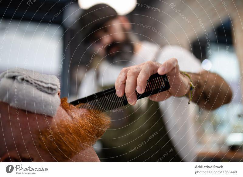 Anonymer Barbier stutzt rothaarigen Herrenbart Männer Klient trendy Friseur Barbershop Vollbart Maskulinität Kunde Pflege Salon gutaussehend stylisch