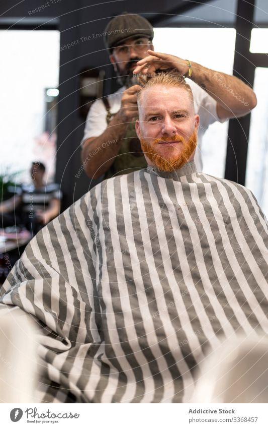 Friseur schneidet einem rothaarigen Mann die Haare Klient trendy Barbershop bärtig Maskulinität Kunde Behaarung Pflege Salon Hipster gutaussehend stylisch
