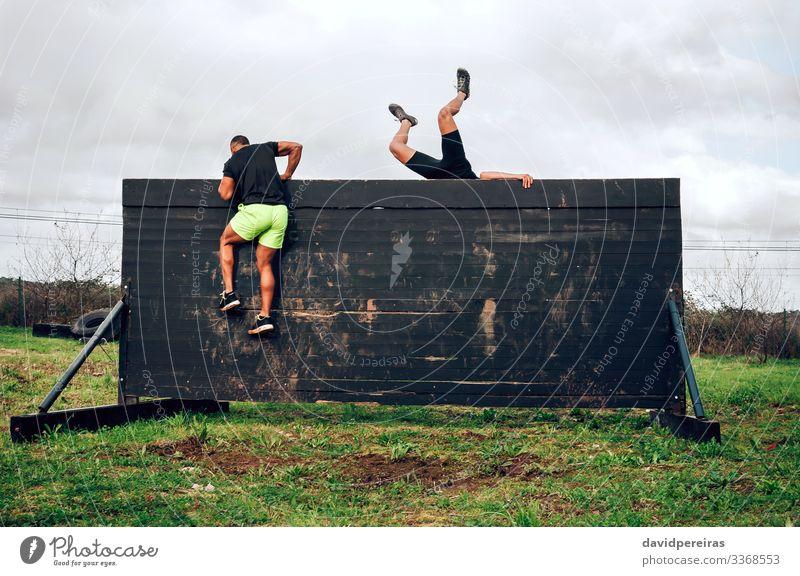 Läufer im Hindernisparcours Kletterwand Lifestyle Sport Klettern Bergsteigen Mensch Mann Erwachsene Menschengruppe springen authentisch stark schwarz anstrengen