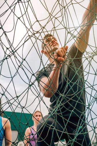 Teilnehmerin am Hindernislauf-Kletternetz Lifestyle Sport Bergsteigen Mensch Mann Erwachsene beobachten authentisch stark anstrengen Konkurrenz Netz
