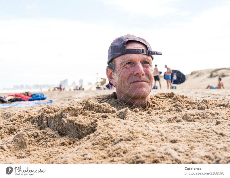 """Mann mit Kappe steckt Kopf aus dem Sand am Strand Farbfoto Außenaufnahme Portrait Kappe,"""" Blau weißer Hintergrund Himmel Sommer Meer Urlaub Menschen eingraben"""