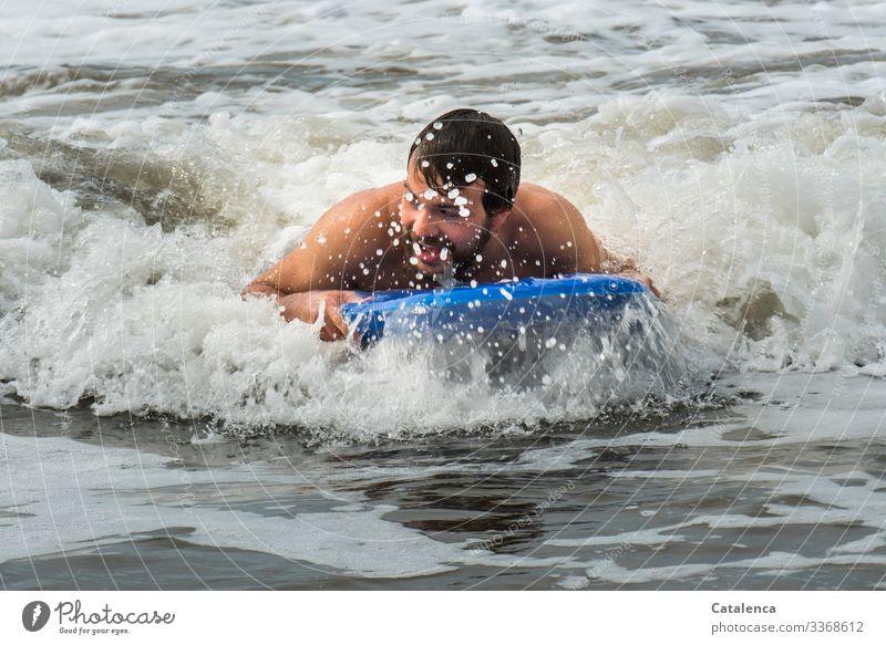 Spaß beim baden im Meer Person männlich junger Mann schwimmen wellenreiten Board Brandung Gischt nass Strand Sommer Blau Grau Freude Ferien Wasser