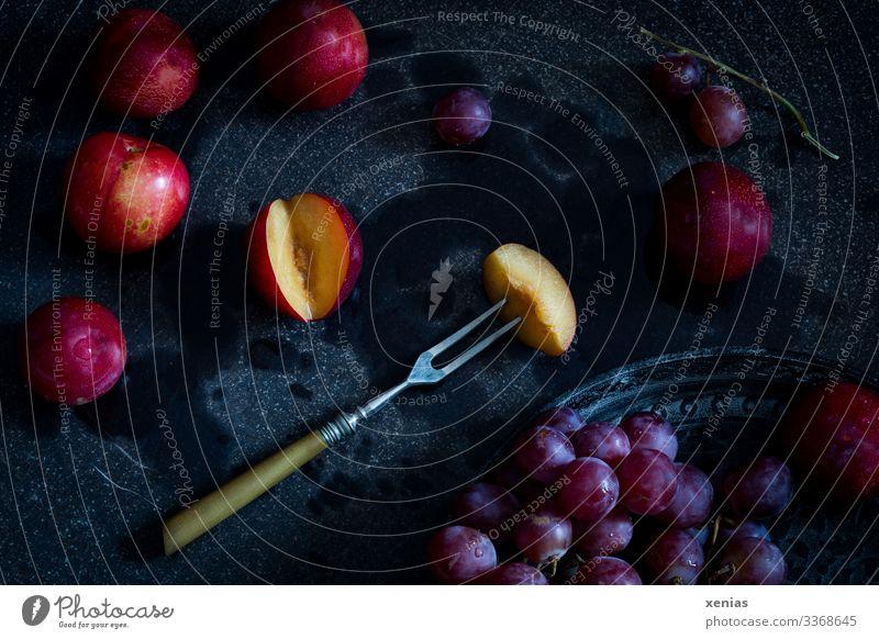 Nektarine mit Gabel und rote Weintrauben auf schwarzem Untergrund Frucht Ernährung Bioprodukte Vegetarische Ernährung Diät Tablett Gesunde Ernährung