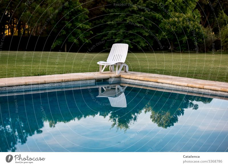 Corona thoughts | Daheim bleiben-      Einsamer Liegestuhl steht am Schwimmbeckenrand, der Himmel spiegelt sich im Wasser, ein gepflegter Rasen und eine Baumreihe sind im Hintergrund zu sehen, die Sonne geht unter.