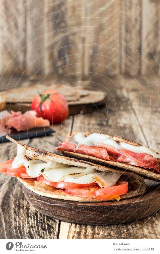 Piadina typisch italienisches Essen Wurstwaren Käse Gemüse Brot Ernährung Mittagessen Vegetarische Ernährung Teller Holz frisch oben schwarz Tradition