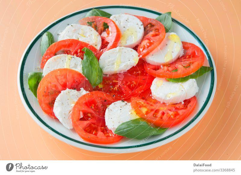 Caprese-Salat auf braunem Hintergrund Käse Gemüse Kräuter & Gewürze Ernährung Essen Diät Teller Tisch frisch rot weiß Tradition Basilikum brauner Hintergrund