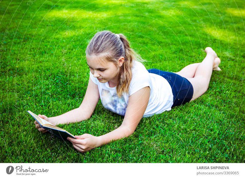 Teenager-Mädchen liegt auf grünem Gras und liest im Park ein Buch Lifestyle Glück schön Gesicht Freizeit & Hobby lesen Sommer Garten Schule lernen Mensch Frau