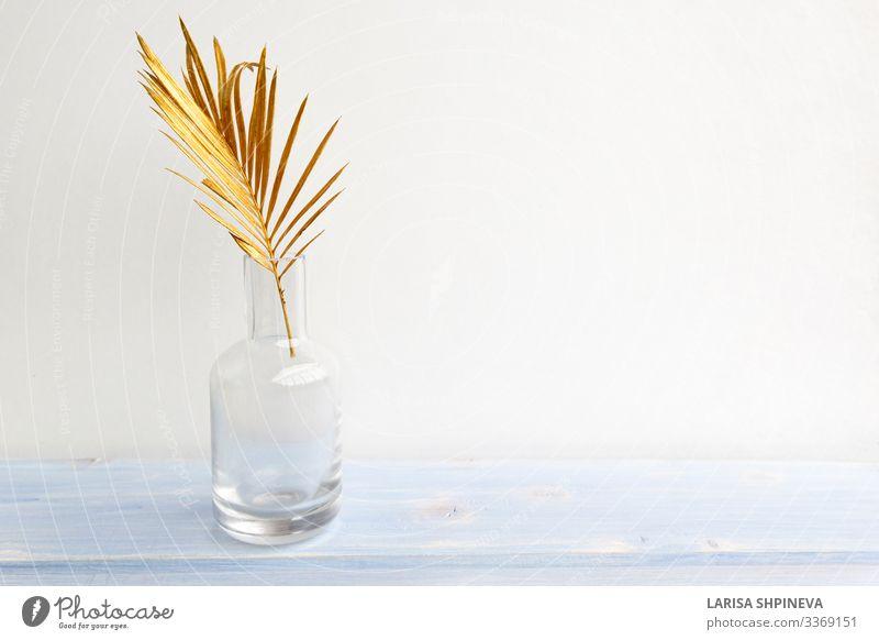 Goldenes Palmenblatt in Glasvasenflasche auf hellem Hintergrund Flasche Reichtum elegant Stil Design exotisch schön Dekoration & Verzierung Tisch Natur Pflanze