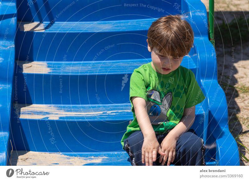 Brasilianischer Junge sitzt auf Spielzeug Treppe des Spielplatzes. Spieltag im Freien. Natur Aktivität wenig bezaubernd Person Brasilianer grün ethnisch