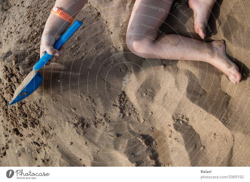 ein Kind spielt barfuß im Sand mit einer Schaufel spielen kind schaufel sand familienurlaub fuss sommer bein wasser spaß junge barfuss leute human natur hand