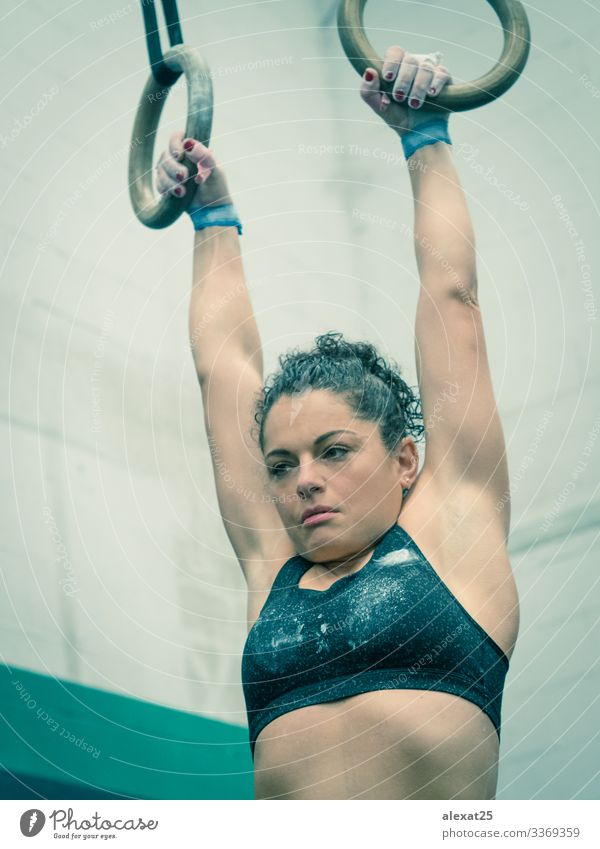 Sportlerin hängt in der Gymnastik an den Ringen Lifestyle Körper Wellness Mensch Frau Erwachsene Hand Fitness muskulös stark Tatkraft anstrengen Bauchmuskeln
