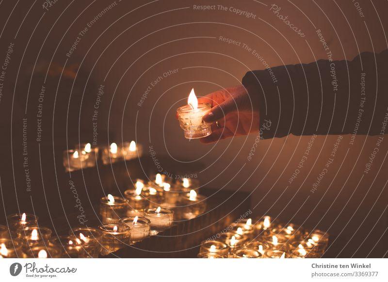 Frau zündet Kerze an einem Kerzenaltar an Erwachsene Hand 1 Mensch 30-45 Jahre 45-60 Jahre Kirche Kerzenschein Kerzenflamme Kerzenglas festhalten leuchten