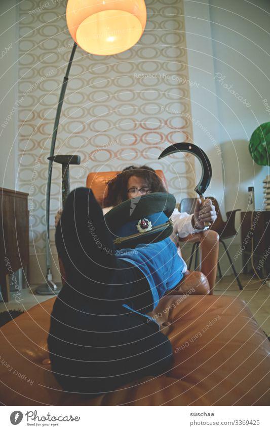 mann auf sessel liegend mit russenmütze auf den knien und sichel und hammer in den händen haltend .. Mann Wohnzimmer Couch Sessel retro sitzend ausgestreckt
