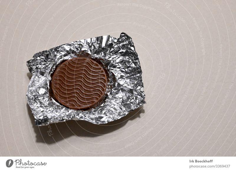 Schokoladentaler Lebensmittel Süßwaren Verpackung Metallfolie Diät Essen genießen glänzend Glück süß braun silber Gefühle Vorfreude Selbstbeherrschung standhaft