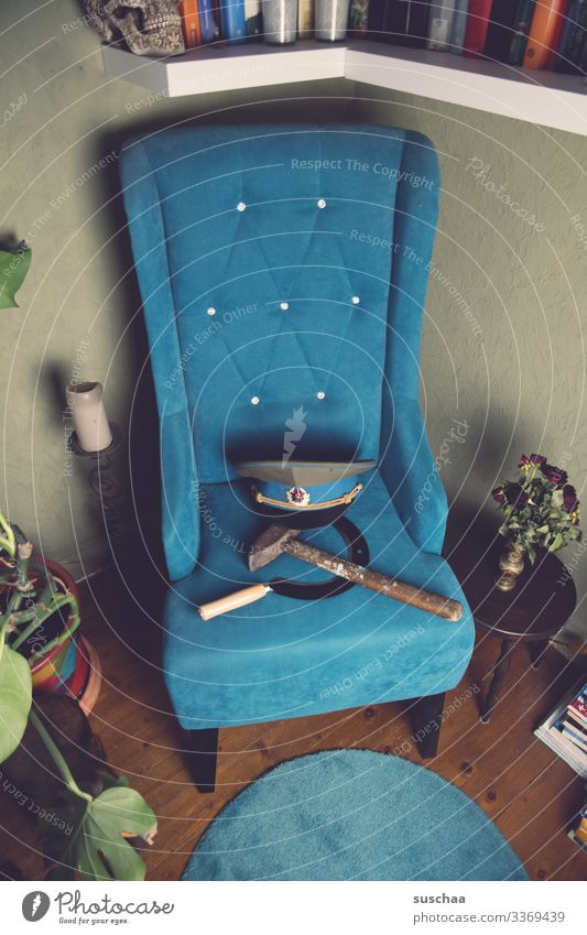 hammer, sichel, totenkopf auf türkisfarbenem sofa in gemütlicher wohnzimmerecke Fotochallenge Hammer Sichel Totenkopf Schädel Sofa Werkzeug Politik & Staat