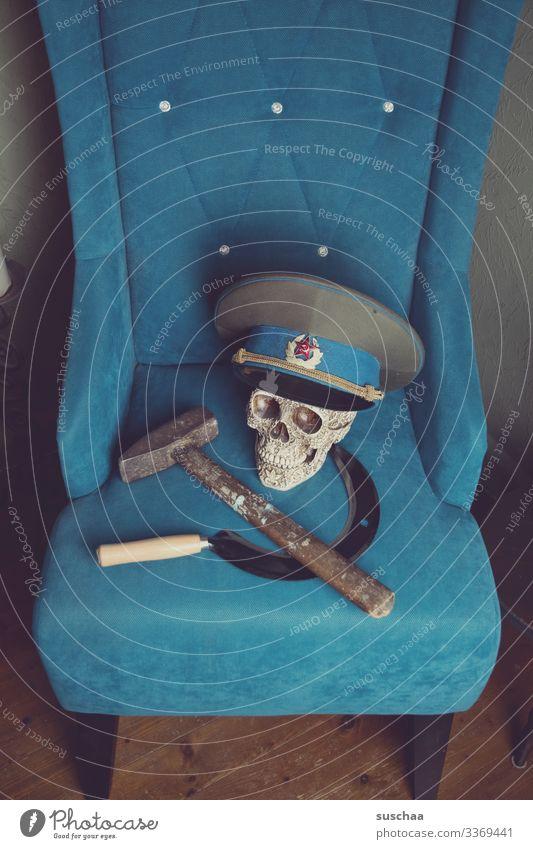 hammer, sichel, totenkopf mit mütze auf türkisfarbenem sofa Fotochallenge Hammer Sichel Totenkopf Schädel Sofa Werkzeug Politik & Staat Russland Sowjetunion