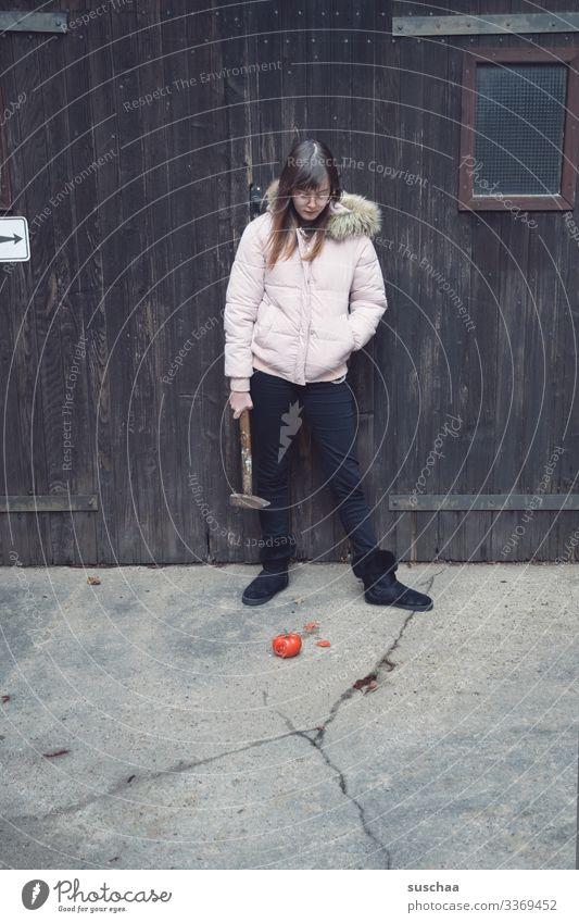 fotochallenge: jugendliche betrachtet eine matschige überreife tomate und überlegt diese mit einem hammer zu zerkleinern Fotochallenge Jugendliche Teenager