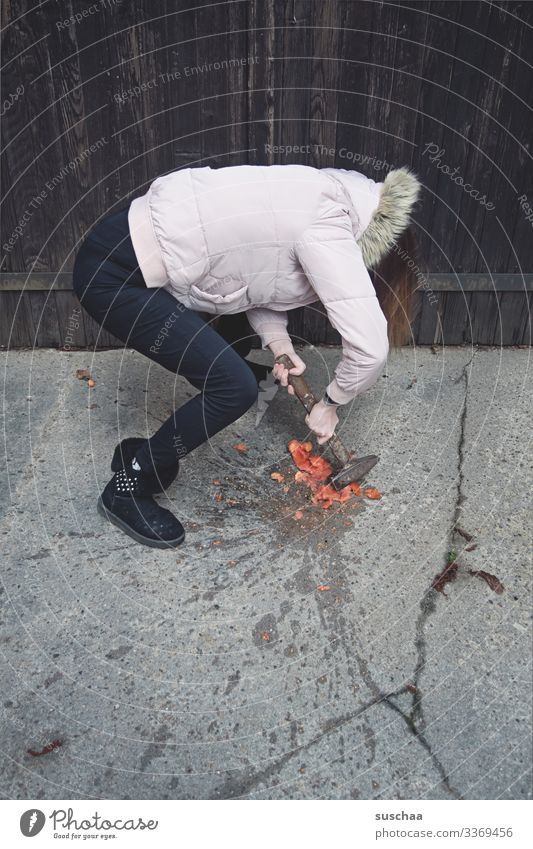 fotochallenge: jugendliche zermatscht eine überreife tomate, die geschmacklich nicht ihren erwartungen entsprach, mit einem hammer Fotochallenge Jugendliche