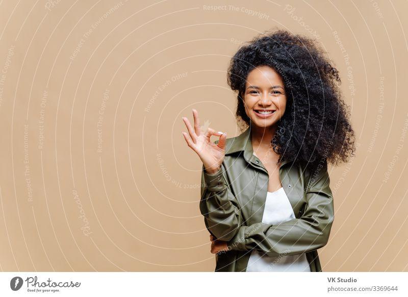 Innenaufnahme einer sympathisch aussehenden, gelockten Frau mit sympathischem Lächeln, gute Geste, ausgezeichnetes Zeichen, gibt Zustimmung, mit modischem Lederhemd bekleidet, isoliert über brauner Wand, links freier Raum
