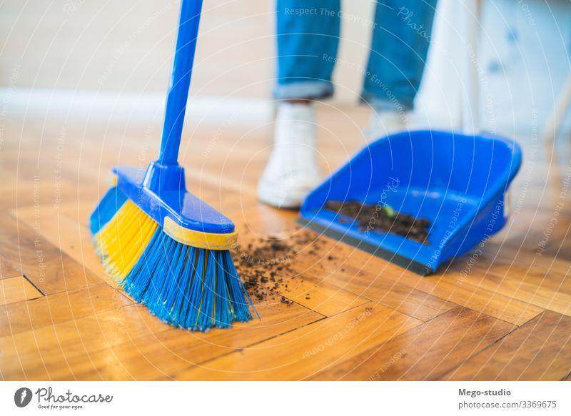 Lateinamerikanischer Mann kehrt zu Hause den Holzboden mit Besen. ausladend Stock heimwärts Hausarbeit Haushalt Haushälterin Objekt im Innenbereich Gerät lebend