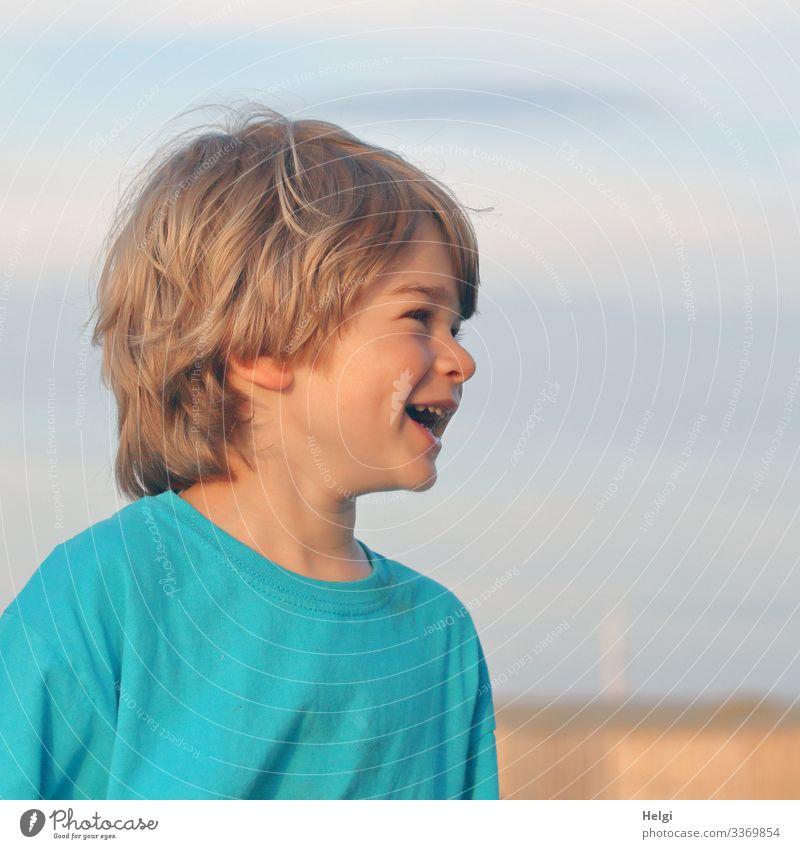 Porträt eines lachenden Kindes, Halbprofil, halblange dunkelblonde Haare, vor blaugrauem Himmel Ferien & Urlaub & Reisen Sommerurlaub Mensch maskulin Kindheit