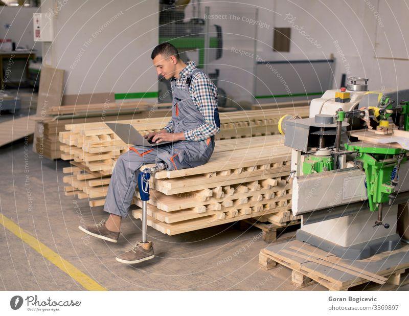 Behinderter junger Mann, der in einer Möbelfabrik arbeitet Arbeit & Erwerbstätigkeit Beruf Handwerker Arbeitsplatz Fabrik Industrie Business Notebook Werkzeug