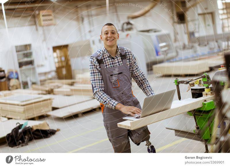 Behinderter junger Mann mit einer Beinprothese, der in einer Fabrik arbeitet Möbel Arbeit & Erwerbstätigkeit Beruf Handwerker Arbeitsplatz Industrie Business