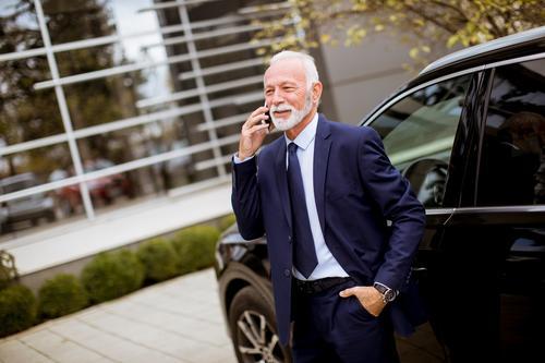 Leitender Geschäftsmann benutzt Mobiltelefon in der Nähe des Autos Lifestyle Reichtum Ferien & Urlaub & Reisen Dekoration & Verzierung Business sprechen Telefon