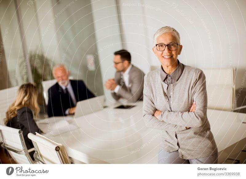 Fröhliche ältere Geschäftsfrau im Büro, während andere Geschäftsleute ein Treffen haben Lifestyle Business Sitzung Mensch Frau Erwachsene Weiblicher Senior 4