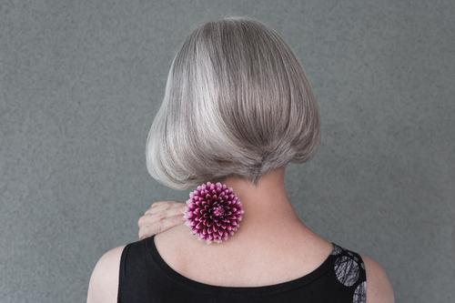 Dame mit schönen silbernen Haaren und roter Dahlie Lifestyle elegant Stil Haare & Frisuren Gesundheitswesen Gartenarbeit Mensch Frau Erwachsene Blume Mode grau