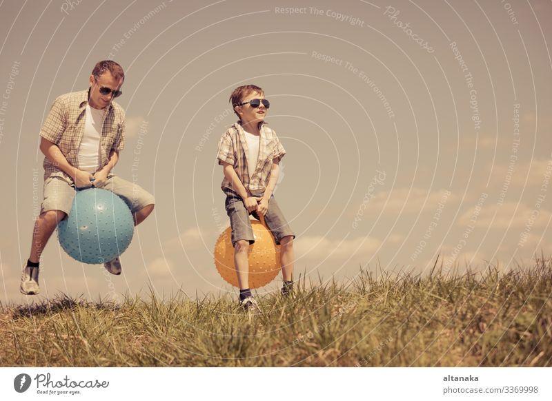 Vater und Sohn spielen zur Tageszeit auf dem Spielfeld. Die Menschen haben Spaß im Freien. Sie springen auf aufblasbaren Bällen auf dem Rasen. Konzept der freundlichen Familie.