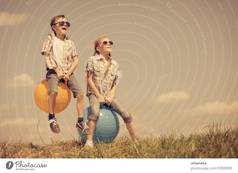 Bruder und Schwester spielen tagsüber auf dem Spielfeld. Kinder haben Spaß im Freien. Sie springen auf aufblasbaren Bällen auf dem Rasen. Konzept der freundlichen Familie.